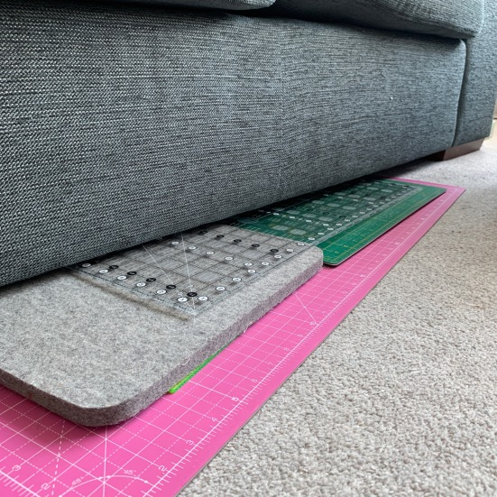 mats and rulers under the sofa